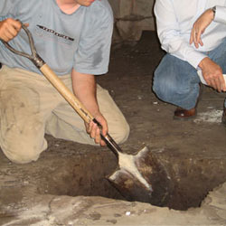 Digging a hole for the engineered fill used in a crawl space support system installation in Tooele