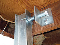 Securing the i-beam system to the top of the floor joist in a foundation wall repair in Sandy.