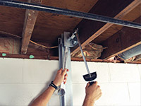 Straightening a foundation wall with the PowerBrace™ i-beam system in a Orem home.