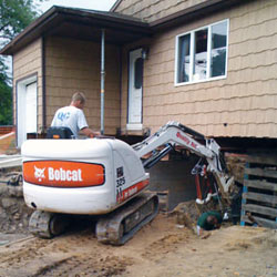 Excavating to expose the foundation walls and footings for a replacement job in Layton