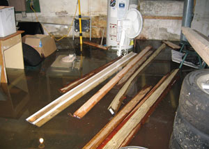 A severely flooding basement in Sandy, with lumber and personal items floating in a foot of water
