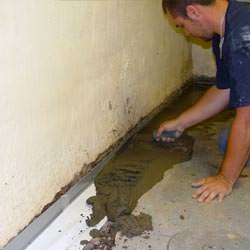 A basement waterproofer installing a perimeter drain system in Cedar City